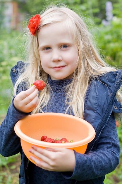 Belle Fille Mangeant Des Fraises Rouges Dans Le Jardin Photo Premium