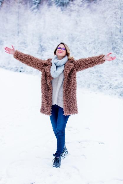 Belle fille en manteau dans une forêt de neige Photo Premium