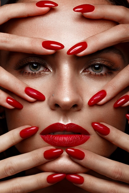 Belle fille avec un maquillage classique et des ongles rouges, conception de manucure, visage beauté, Photo Premium