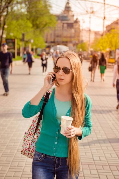 Belle Fille Marchant Dans La Rue Avec Du Café Et Parler Au Téléphone Photo Premium