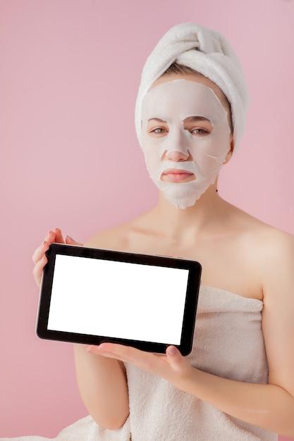 Belle Fille Avec Un Masque De Tissu Et Une Tablette Dans Leurs Mains Avec Copie Espace Sur Un Espace Rose Photo Premium
