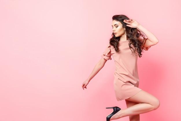 Belle Fille à La Mode Avec De Longs Cheveux Bouclés Dans Une Robe Rose En Studio Sur Fond Rose. Photo Premium