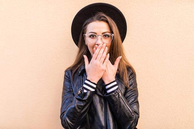 Belle Fille De Mode Timide En Veste De Cuir Et Chapeau Noir Isolé Sur Mur Jaune Clair Photo gratuit