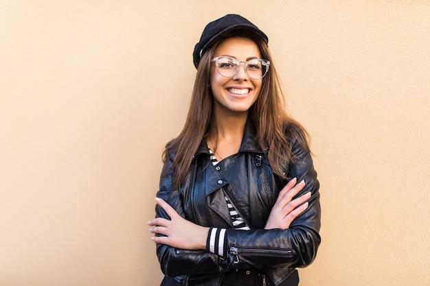 Belle Fille De Mode En Veste De Cuir Et Chapeau Noir Tenir Les Bras Croisés Isolé Sur Mur Jaune Clair Photo gratuit