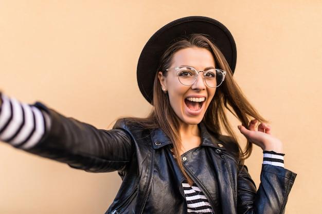 Belle Fille De Mode En Veste De Cuir, Lunettes Transparentes Et Chapeau Noir Fait Selfie Isolé Sur Mur Jaune Clair Photo gratuit
