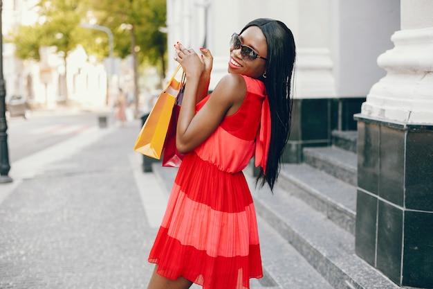Belle fille noire avec des sacs dans une ville Photo gratuit