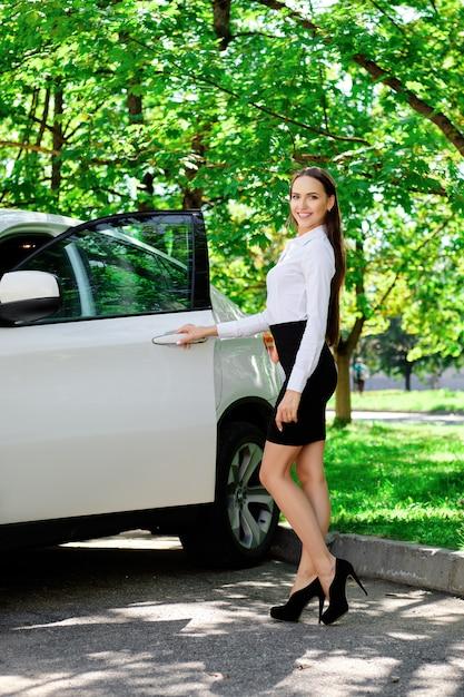 Belle fille ouvre la portière de sa voiture et va s'asseoir sur le siège du conducteur Photo Premium