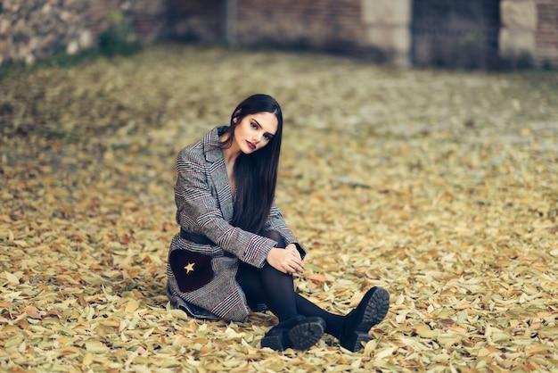 Belle fille porte manteau d'hiver assis sur le sol d'un parc urbain plein de feuilles d'automne. Photo Premium