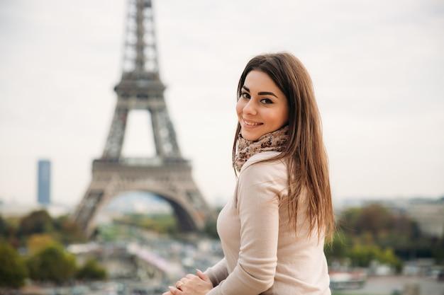 Belle Fille Posant Au Photographe Dans Le Contexte De La Tour Eiffel. L'automne Photo Premium
