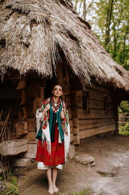Belle fille pose sur les cours près de la maison dans une robe traditionnelle ukrainienne Photo gratuit