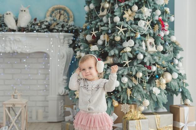 Belle fille près d'arbre de noël décoré avec cheval à bascule en bois jouet. bonne année. portrait petite fille. Photo Premium