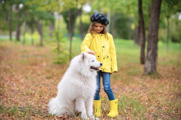 Belle fille sur une promenade avec un beau chien dans un parc en plein air Photo Premium
