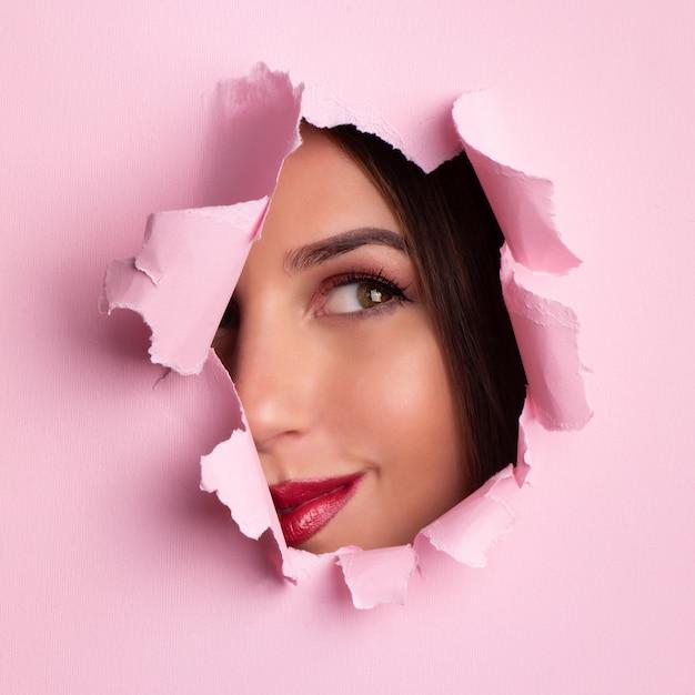 Belle fille regarde à travers le trou dans le fond de papier rose. Photo Premium