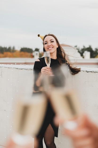 Belle fille en robe noire sur le fond de remonter des verres de champagne Photo gratuit