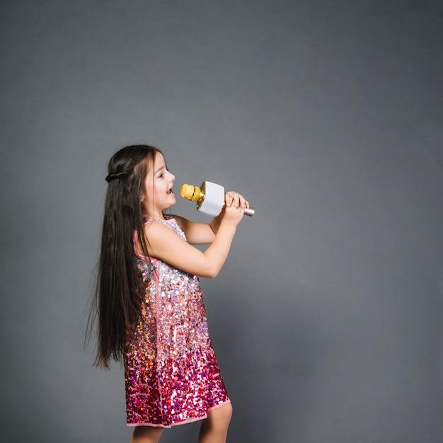 Belle fille en robe de paillettes en signant la chanson avec microphone Photo gratuit