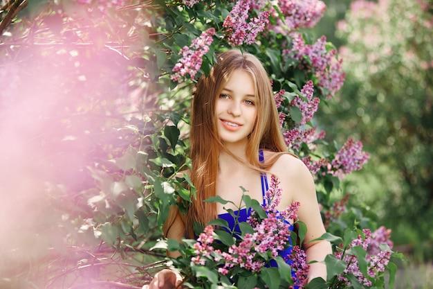 Belle fille en robe posant près de bush de lilas Photo Premium