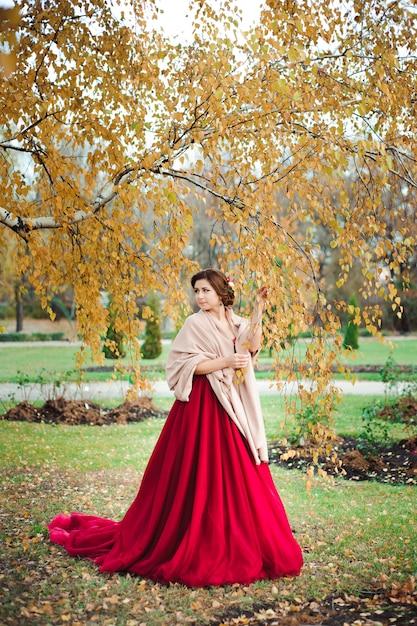 Belle fille en robe rouge dans la forêt d'automne Photo Premium