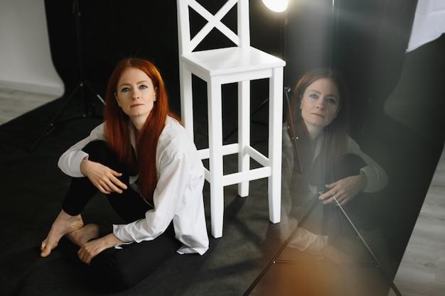 Belle fille rousse assise sur le sol en studio Photo gratuit