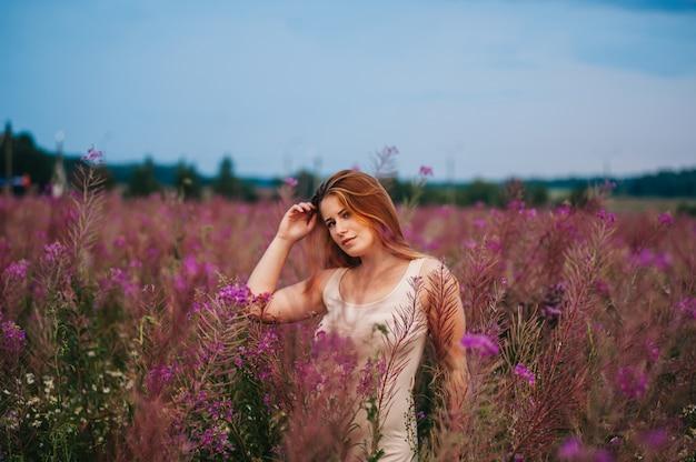 Belle fille rousse vêtue d'une robe dans un champ de fleurs de thé au saule. Photo Premium