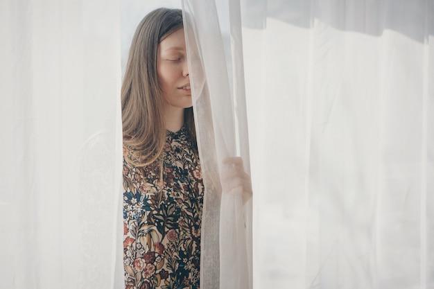 Une Belle Fille Sans Maquillage Regarde De Derrière Le Rideau, Une Femme à La Fenêtre. Publicité Maquillage Naturel, Passe-temps Du Matin Photo Premium