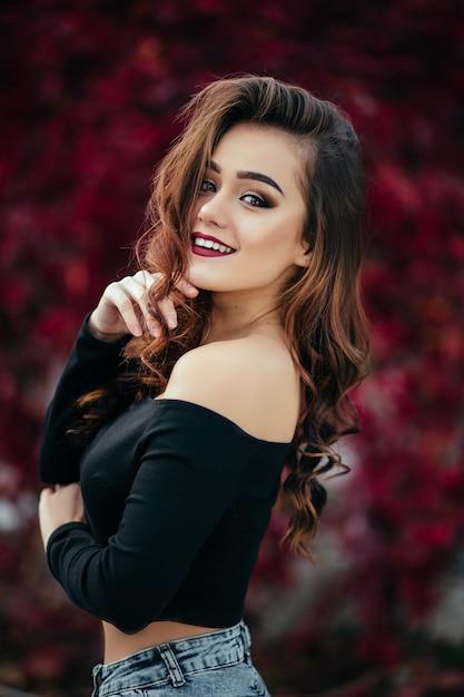 La belle fille se tient près de walll avec des feuilles Photo gratuit