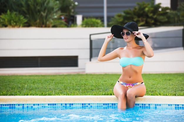 Belle fille sexy bronzée en bikini et chapeau noir se faire bronzer au bord d'une piscine Photo Premium