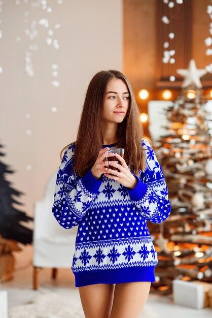 Belle fille souriante dans un pull chaud de vacances avec une tasse de thé chaud Photo Premium
