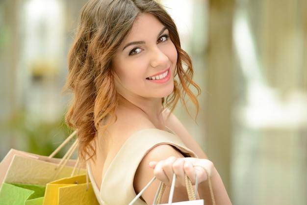 Belle fille sourit et porte des sacs. Photo Premium