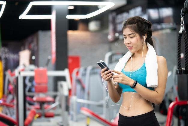 Belle fille sportive avec écouteurs et smartphone marcher ou courir sur tapis roulant à la gym Photo Premium