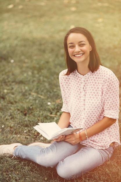 Belle fille tenant un livre ouvert Photo gratuit