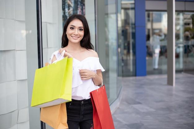Belle fille tenant des sacs à provisions et souriant tout en faisant des achats dans le supermarché / centre commercial Photo Premium