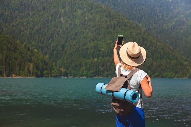 Belle fille voyageur fait selfie sur un grand lac de montagne bleue dans le fond des montagnes Photo Premium