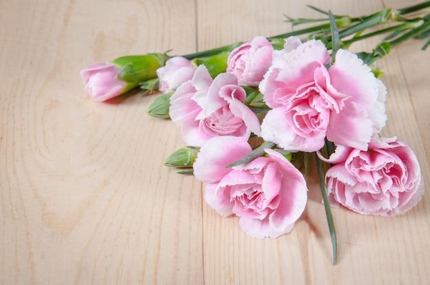 Belle fleur d'oeillets en fleurs sur un fond de bois Photo Premium