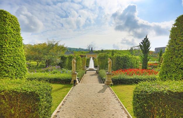 Belle fontaine dans le jardin de fleurs. Photo Premium