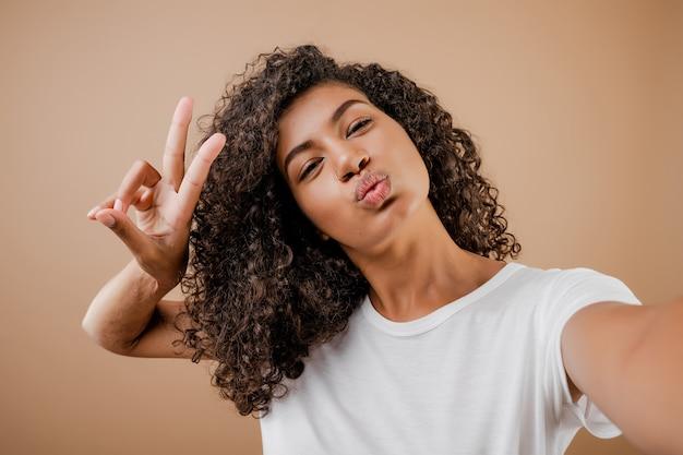 Belle Heureuse Jeune Femme Noire Faisant Selfie Isolé Sur Marron Photo Premium