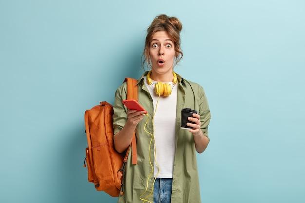 Une Belle Hipster Excitée Ouvre La Bouche De La Surprise, Lit Des Nouvelles Sur Internet, Utilise Un Téléphone Portable Moderne Et Des écouteurs Pour écouter De La Musique Ou Un Livre Audio, Tient Un Café à Emporter, Suit Des Cours Photo gratuit