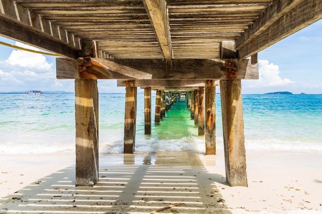 Belle image éclaboussant la vague de la mer sous le vieux pont de béton et de bois. Photo Premium