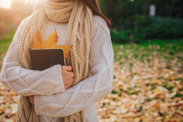 Belle Jeune Brune Assise Sur Une Feuille D'automne Tombée Dans Un Parc, Lisant Un Livre. Photo Premium