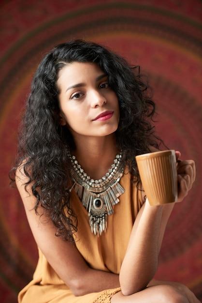 Belle jeune brune frisée posant et tenant la tasse Photo gratuit