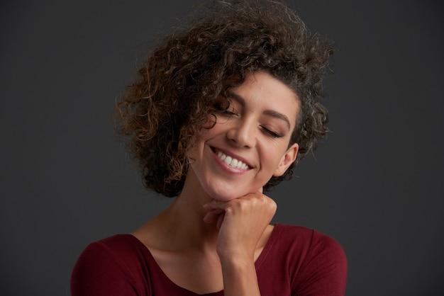 Belle jeune brunette caucasienne frisée qui pose en studio avec les yeux fermés Photo gratuit