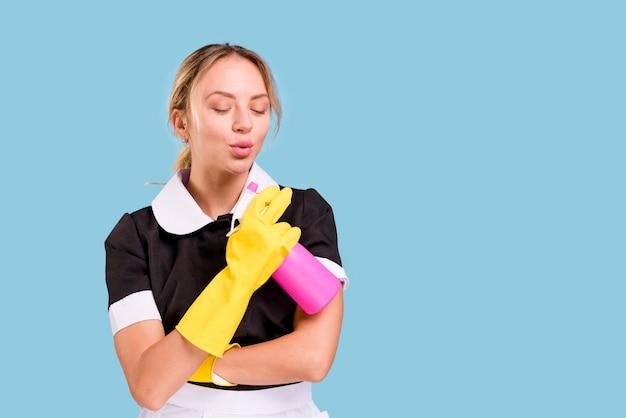 Belle jeune concierge tenant un vaporisateur et soufflant avec les yeux fermés sur fond bleu Photo gratuit