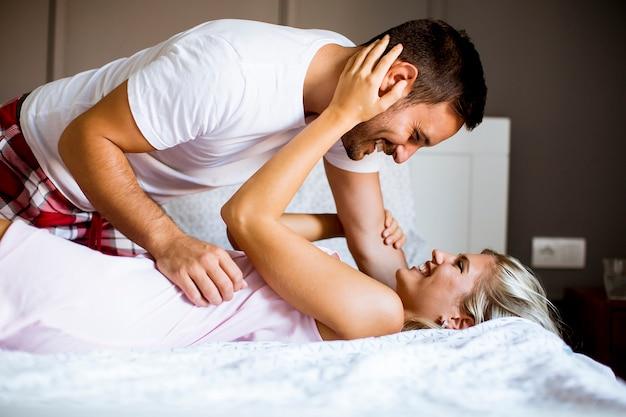 Belle jeune couple dans le lit Photo Premium