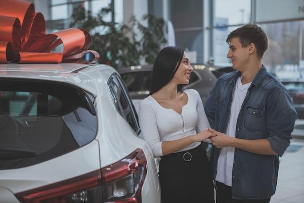 Belle jeune couple marié, acheter une nouvelle voiture ensemble Photo Premium