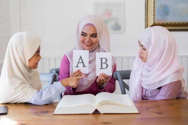 Belle jeune enseignant musulman tenant deux feuilles blanches et de jolies filles musulmanes asiatiques en salle de classe. Photo Premium