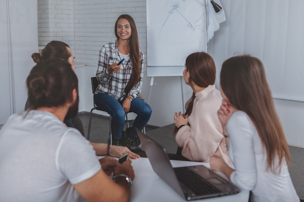 Belle jeune femme d'affaires menant une réunion au bureau Photo Premium
