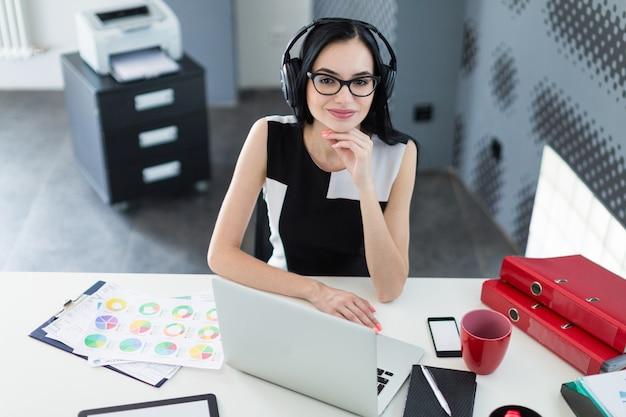 Belle Jeune Femme D'affaires En Robe Noire, Des écouteurs Et Des Lunettes S'asseoir à La Table Et Travaille Sur Un Ordinateur Portable Photo Premium