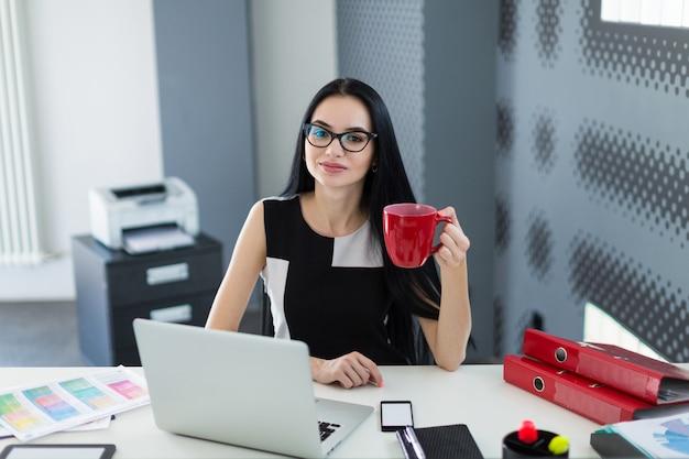 Belle jeune femme d'affaires en robe noire et lunettes s'assoit à la table et travaille avec le café à la main Photo Premium