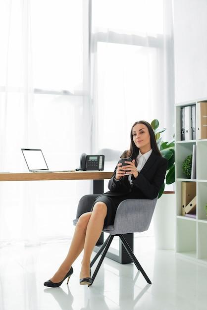 Belle jeune femme d'affaires tenant une tasse de café jetable en main assis sur une chaise Photo gratuit
