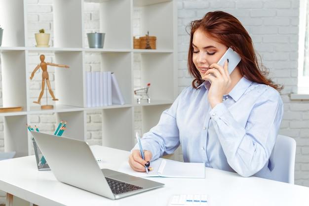 Belle jeune femme d'affaires utilise un smartphone, travaille au bureau Photo Premium
