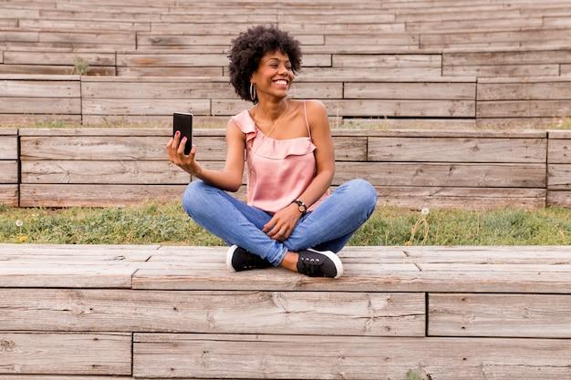 Belle Jeune Femme Afro-américaine à L'aide De Téléphone Portable, Assis Sur Des Escaliers En Bois Et Souriant. Fond Bois. Mode De Vie à L'extérieur Photo Premium